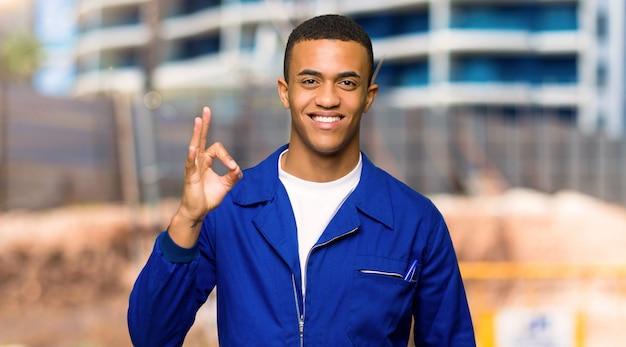 De jonge mens die van de afro amerikaanse arbeider een ok teken met vingers in een bouwwerf toont