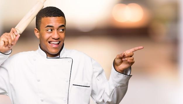De jonge mens die van de afro amerikaanse chef-kok aan de kant richten en een product voorstellen op unfocused achtergrond