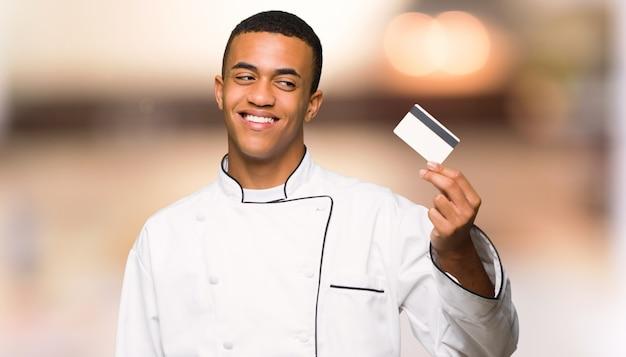 De jonge mens die van de afro amerikaanse chef-kok een creditcard houden en op unfocused achtergrond denken