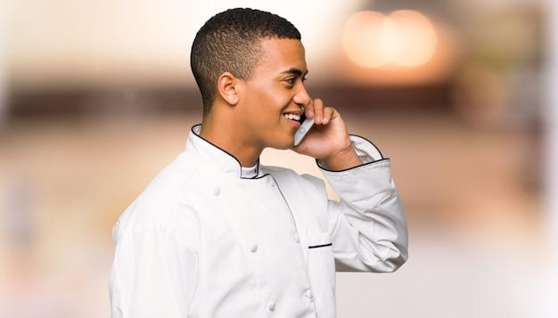 De jonge mens die van de afro amerikaanse chef-kok een gesprek met de mobiele telefoon houden op ongericht muur