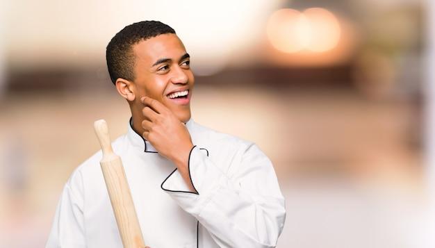 De jonge mens die van de afro amerikaanse chef-kok een idee denken terwijl het krassen van hoofd op ongericht achtergrond