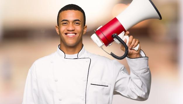 De jonge mens die van de afro amerikaanse chef-kok een megafoon houden unfocused achtergrond