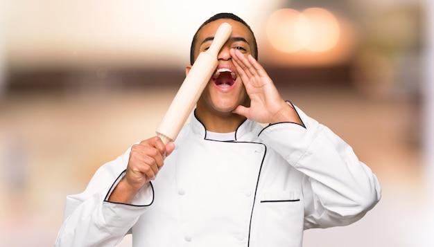De jonge mens die van de afro amerikaanse chef-kok en iets schreeuwen aankondigen unfocused achtergrond