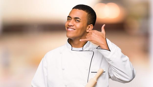 De jonge mens die van de afro amerikaanse chef-kok telefoongebaar maakt. bel me terug teken op ongericht muur