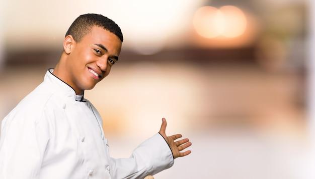 De jonge mens die van de afro amerikaanse chef-kok terug en een product op voorstellen ongericht achtergrond
