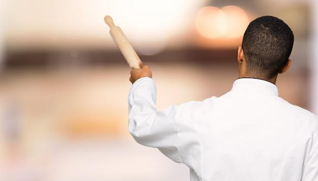 De jonge mens die van de afro amerikaanse chef-kok terug met de wijsvinger richten op ongericht muur