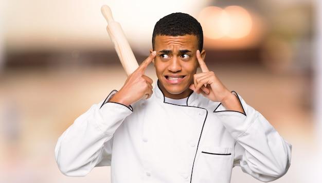 De jonge mens die van de afro amerikaanse chef-kok twijfels hebben en op unfocused achtergrond denken