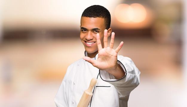 De jonge mens die van de afro amerikaanse chef-kok vijf met vingers tellen op ongericht muur