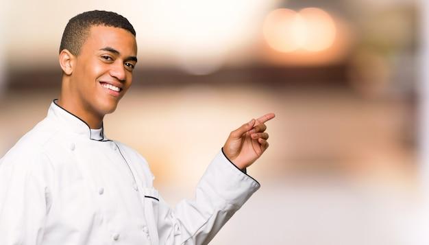 De jonge mens die van de afro amerikaanse chef-kok vinger aan de kant in zijpositie aangaande ongericht muur richten