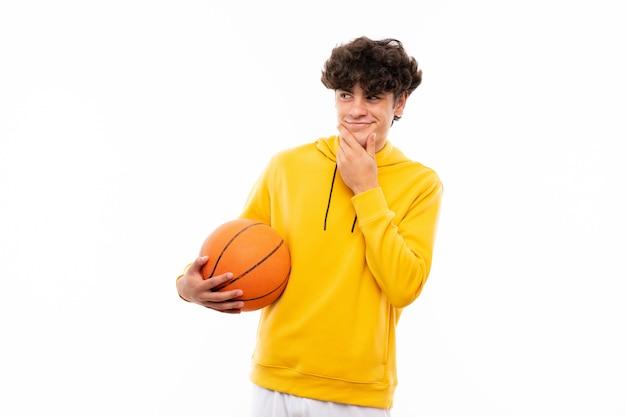 De jonge mens die van de basketbalspeler over geïsoleerde witte muur een idee denkt