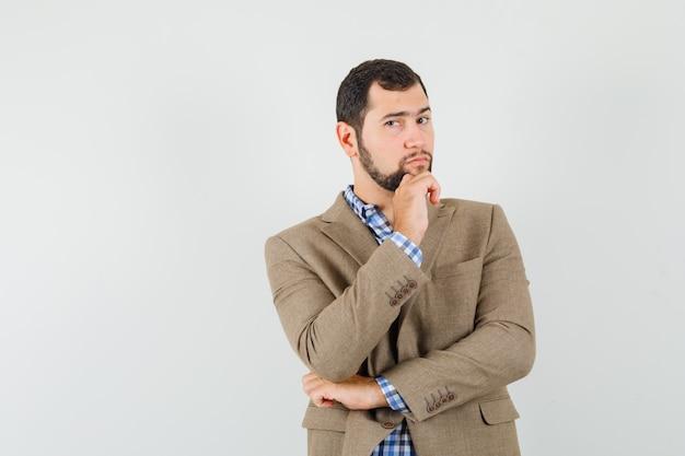 De jonge mens die zich in het denken bevindt stelt in overhemd, jasje en kijkt verstandig.