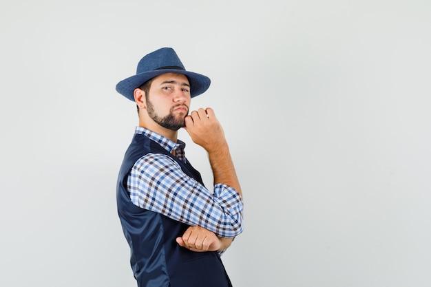 De jonge mens die zich in het denken bevindt stelt in overhemd, vest, hoed en ziet er knap uit.