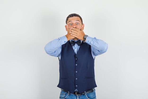 De jonge mens die zijn mond behandelt met dient kostuum, spijkerbroek in en kijkt bang