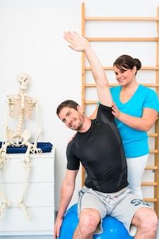 De jonge mens doet uitrekkende oefeningen met fysiotherapeut