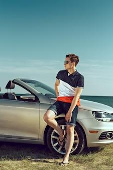 De jonge mens drijft een auto op het strand