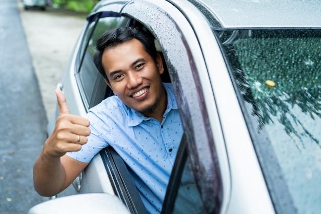 De jonge mens drijft een auto opent het venster, glimlacht, en toont duim