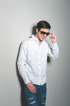 De jonge mens in borrels en wit overhemd glimlacht status dichtbij de muur met glazen