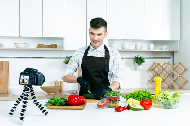 De jonge mens in bruine schort schiet videoblog over koken