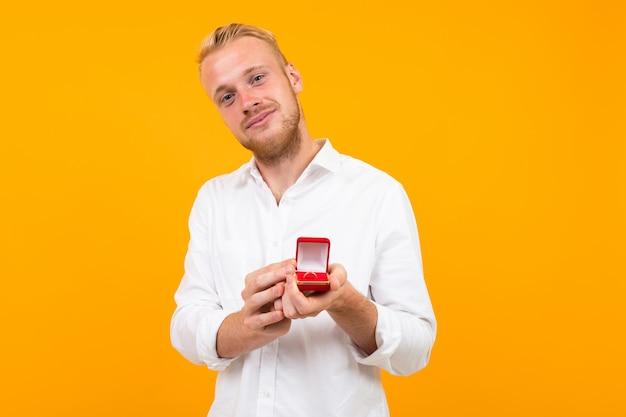 De jonge mens in een wit overhemd doet een huwelijksaanzoek aan een meisje dat een ring op een gele achtergrond houdt