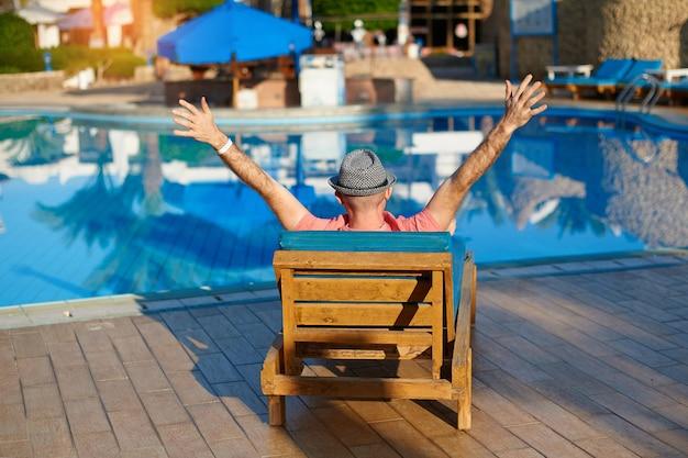 De jonge mens in hoed ligt op louger dichtbij zwembad voor ontspant rust in egypte
