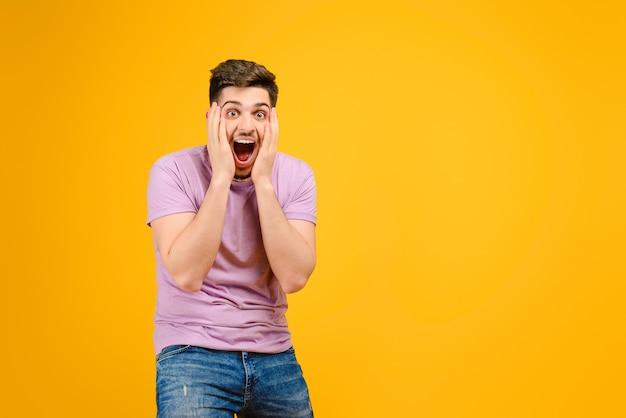 De jonge mens is gelukkig en opgewekt geïsoleerd over gele achtergrond