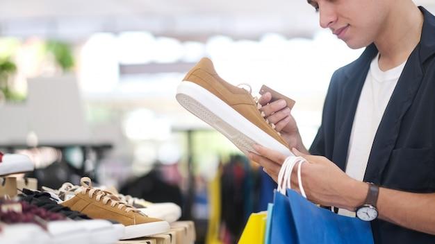 De jonge mens kiest schoen terwijl het doen bij het winkelcomplex winkelen.