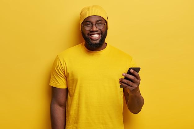 De jonge mens kleedde zich in gele holdingstelefoon