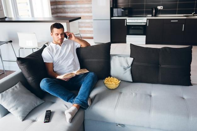 De jonge mens las boek en spreekt tegelijkertijd op telefoon.