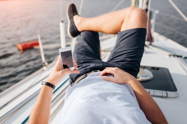 De jonge mens ligt op jachtraad en het koelen. hij houdt de telefoon in linkse hand. de juiste is op de buik. hij houdt rechterbeen links. de mens heeft vakantie. hij draagt een wit overhemd en een zwarte korte broek met schoenen.
