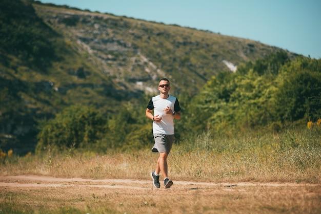 De jonge mens loopt of jogt op een plattelandspat