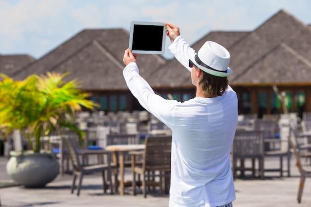 De jonge mens maakt een foto op tabletcomputer bij tropisch strand