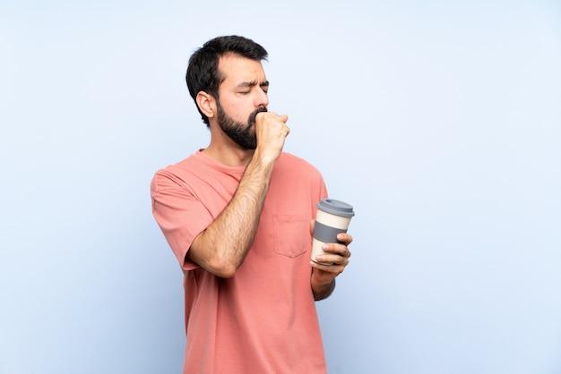 De jonge mens met baard die haalt koffie over geïsoleerd blauw houdt lijdt met hoest en voelt slecht