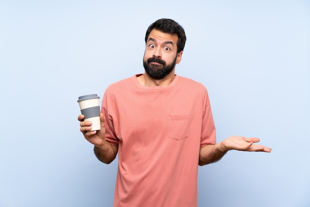 De jonge mens met baard die haalt koffie over geïsoleerd blauw weg hebbend twijfels terwijl het opheffen van handen