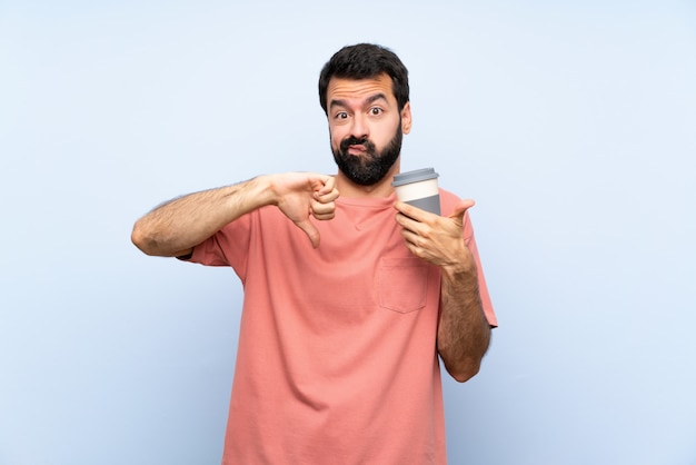 De jonge mens met baard die haalt koffie over geïsoleerd blauw weg maakt goed-slecht teken. onbeslist tussen ja of niet