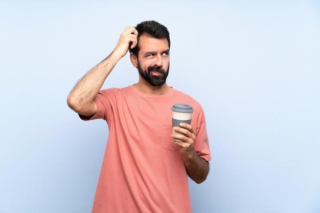 De jonge mens met baard die haalt koffie over geïsoleerde blauwe muur houden die twijfels hebben terwijl het krassen van hoofd