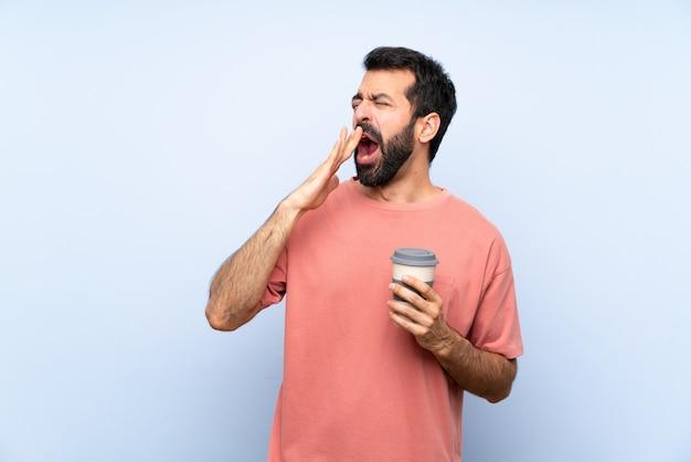 De jonge mens met baard die haalt koffie over geïsoleerde blauwe muur houden geeuwend en behandelend wijd open mond met hand