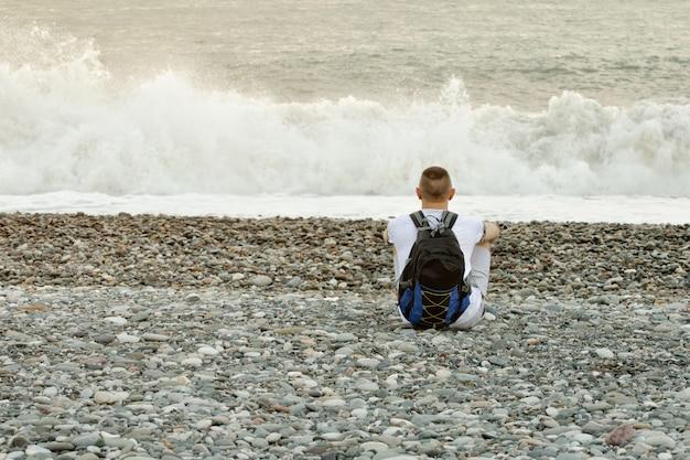 De jonge mens met een rugzak zit op de oceaankust. uitzicht vanaf de achterkant