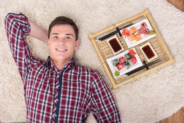 De jonge mens met sushi ligt thuis op de vloer.