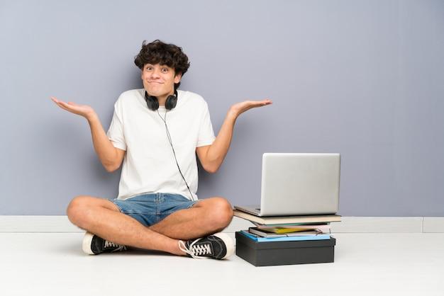 De jonge mens met zijn laptop zitting één de vloer die twijfels hebben met verwart gezichtsuitdrukking