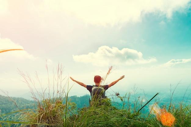 De jonge mens neemt zijn handen op hemel met gelukkig op en voelt vrijheid in zonsondergang bij berg.