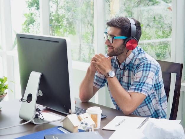 De jonge mens ontspant thuis met oortelefoon