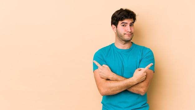 De jonge mens op beige muur wijst zijdelings