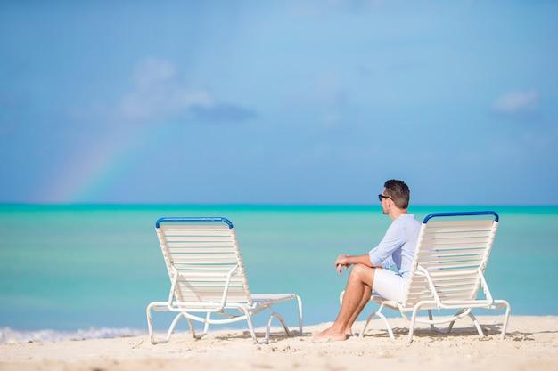 De jonge mens op het strand rust op sunbed alleen openlucht