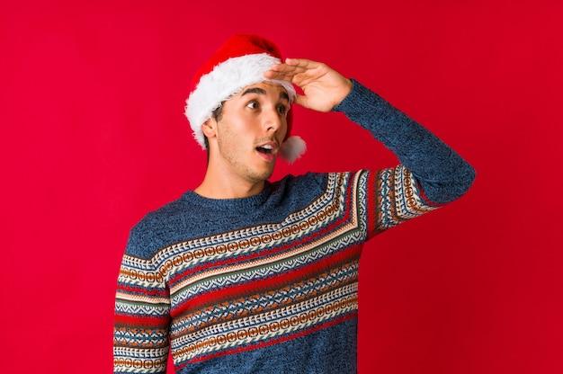De jonge mens op kerstmisdag haalt schouders op en verwarde open ogen.