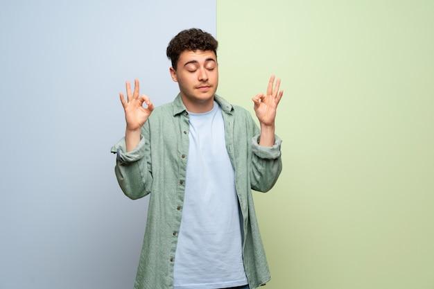De jonge mens over blauwe en groene achtergrond in zen stelt