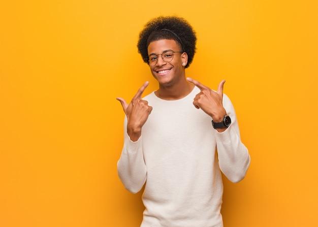 De jonge mens over een oranje muur glimlacht, wijzend mond