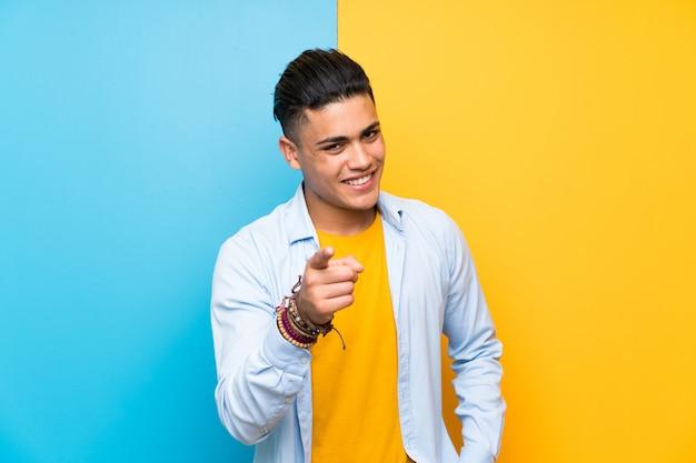 De jonge mens over geïsoleerde kleurrijke achtergrond richt vinger op u