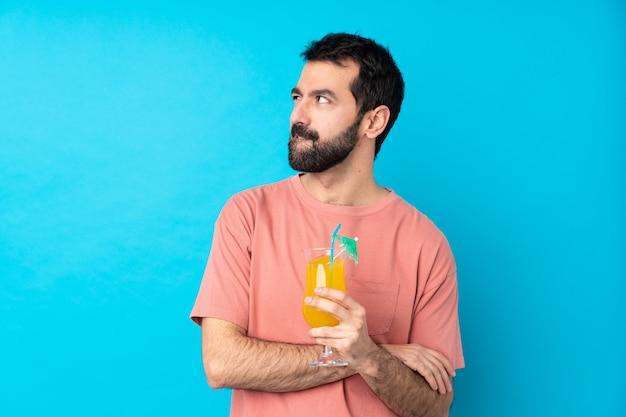 De jonge mens over het houden van een cocktail over geïsoleerde blauwe muur met verwart gezichtsuitdrukking