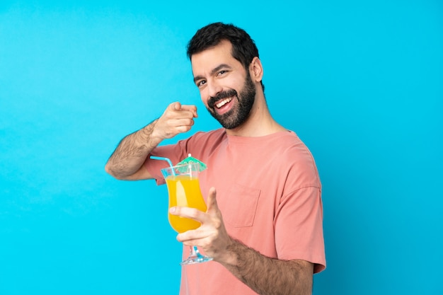 De jonge mens over het houden van een cocktail over geïsoleerde blauwe muur richt vinger op u terwijl het glimlachen