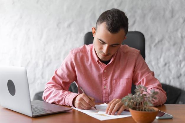 De jonge mens schrijft bij zijn bureau in het bureau.